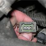 Чтобы снять колодку с проводами от датчика скорости, сжимаем пружинные зажимы пальцами