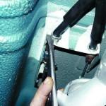 Выньте наконечник оболочки троса из кронштейна на кузове