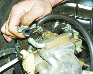 Ослабляем хомут и снимаем шланг подачи ОЖ от штуцера подогрева дроссельного патрубка