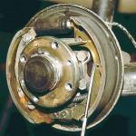 Отверткой выводим из зацепления с колодкой направляющую пружину