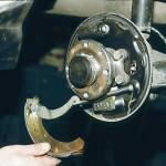 Отсоединив направляющую пружину от задней тормозной колодки, выводим рычаг ручного привода колодок из наконечника троса