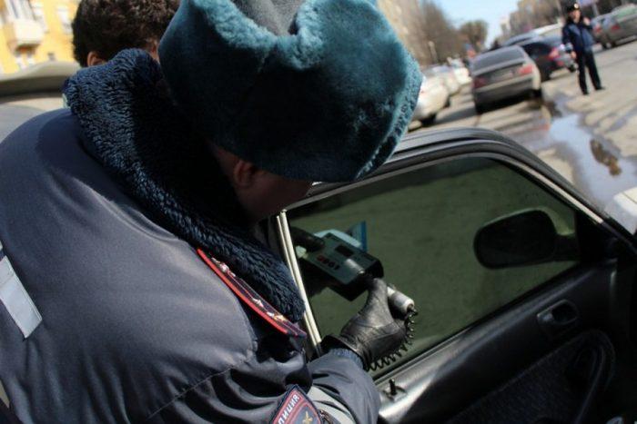 Инспектор ГИБДД проверяет уровень светопропускаемости тонировки