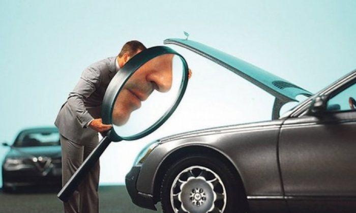 мужчина рассматривает машину через лупу