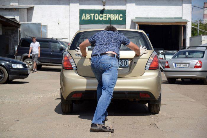 мужчина толкает авто в сервис